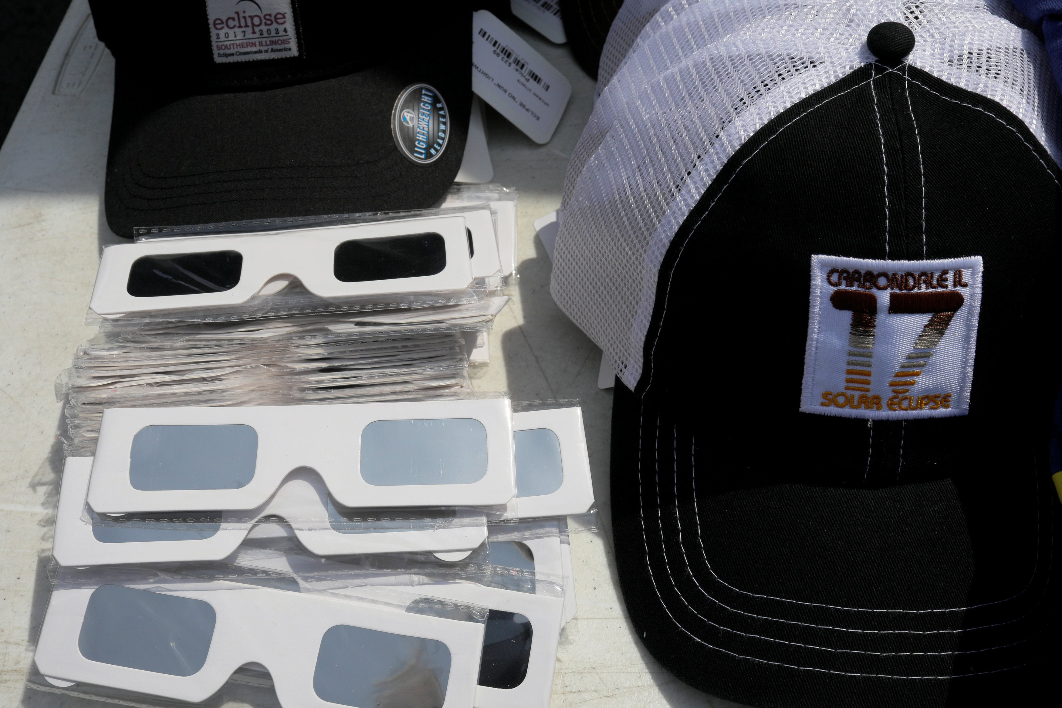 Solar viewing glasses and baseball caps are for sale in Carbondale