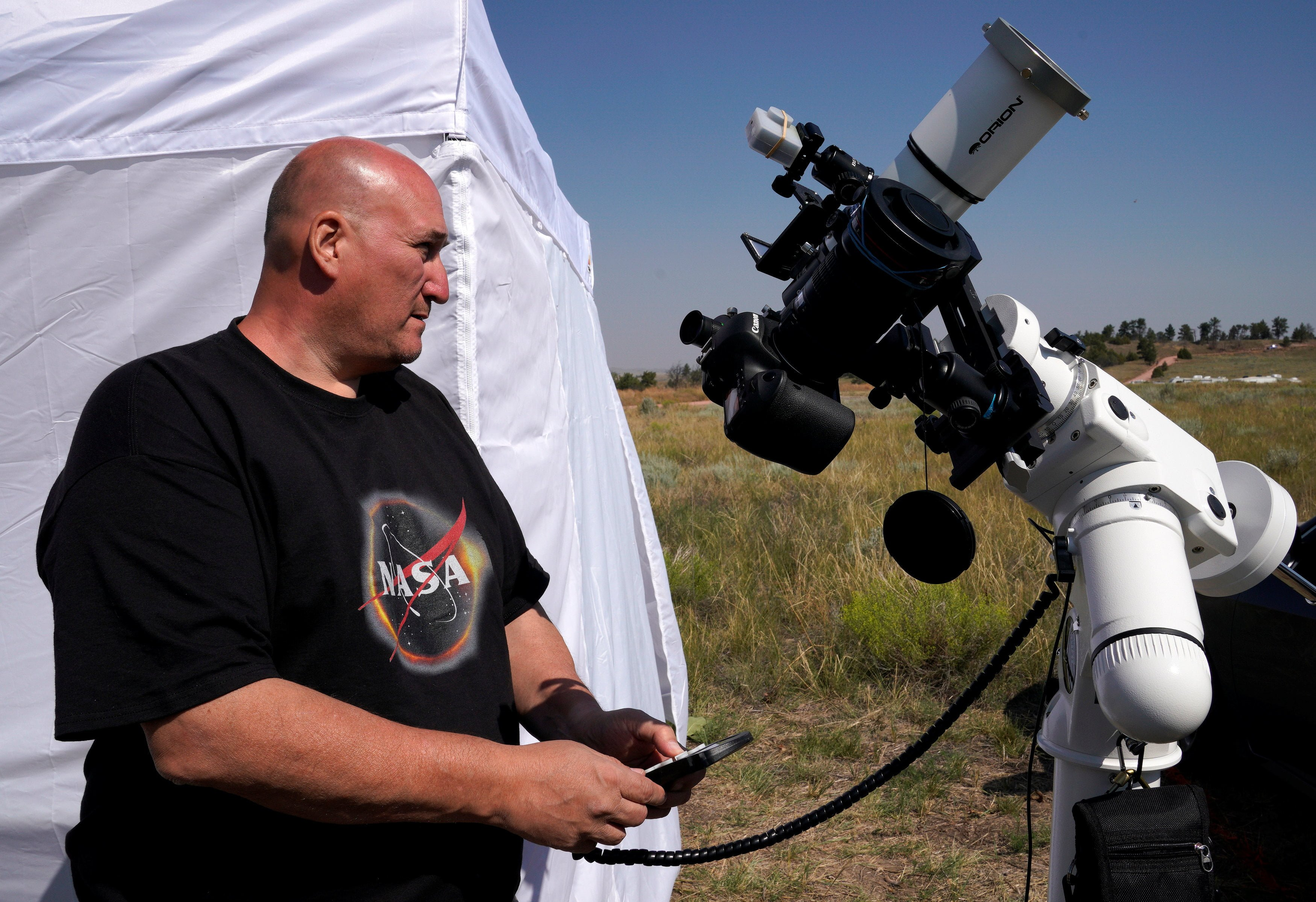 Rick Roty works with his telescope in a designated eclipse viewing area in a campground near Guernsey