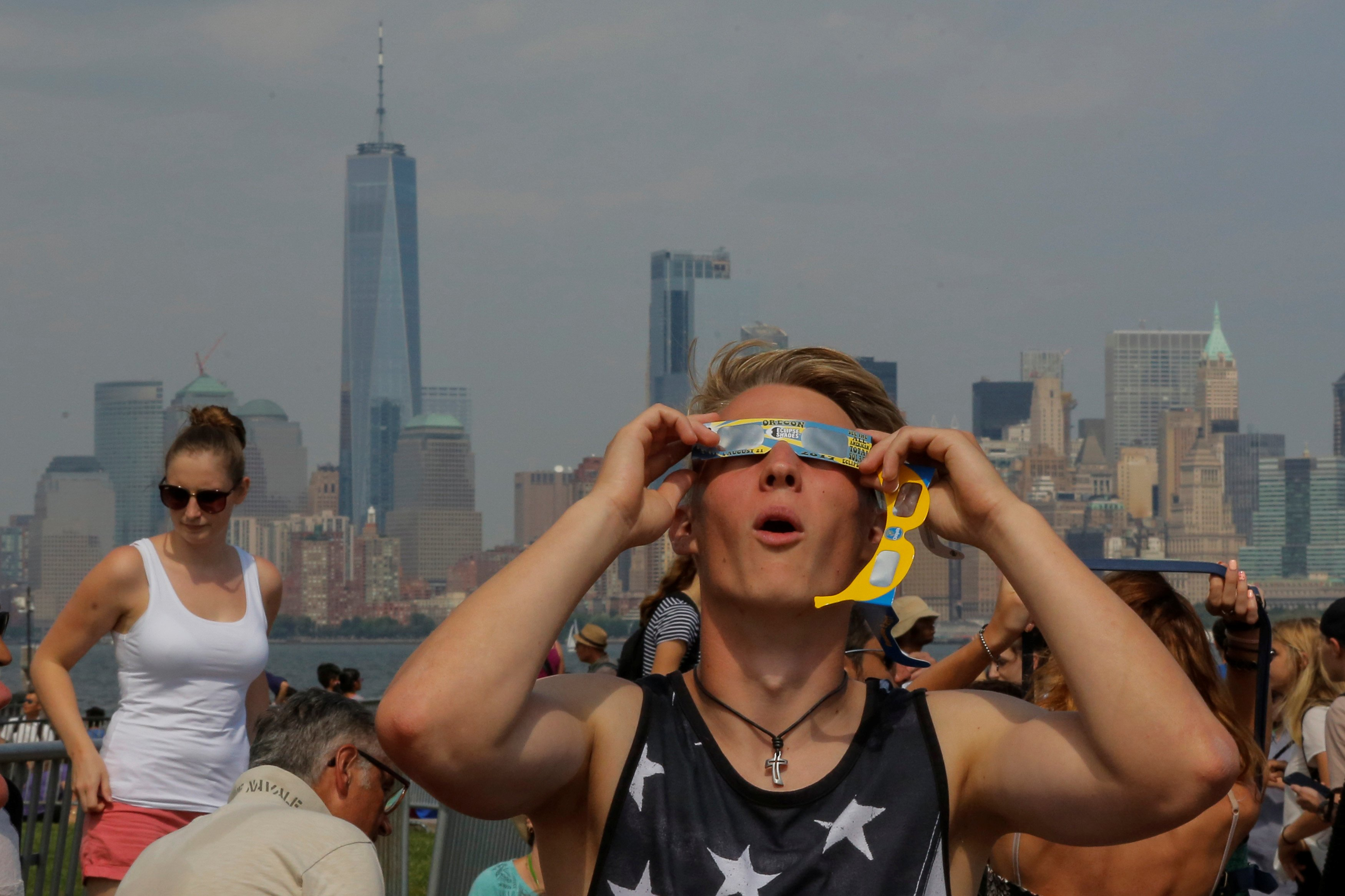 A man takes a look at the solar eclipse at Liberty State Island as the Lower Manhattan and One World Trade center are seen in the background in New York