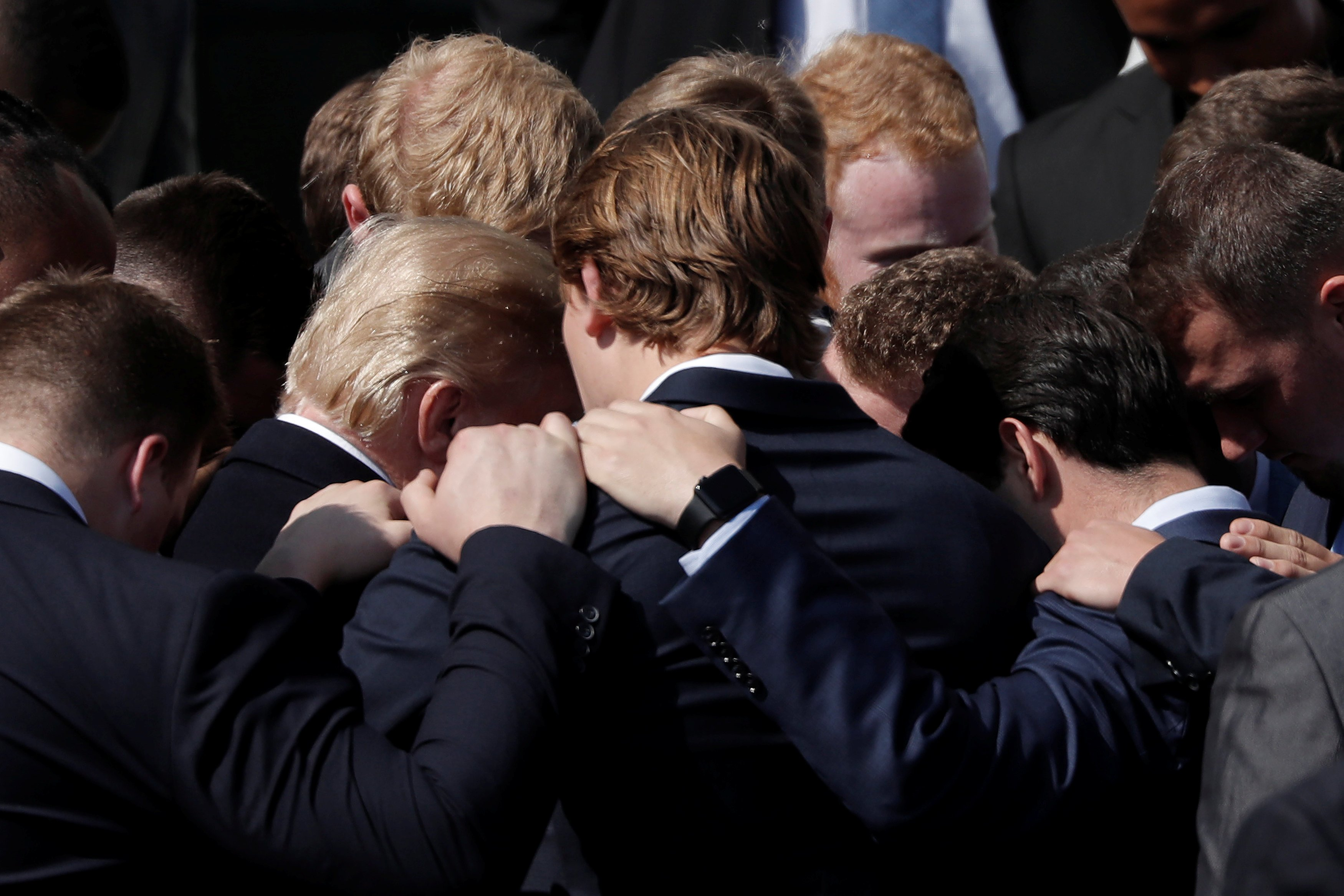 U.S. President Donald Trump prays with team members of the 2017 NCAA Football National Champions, The Alabama Crimson Tide during an event hosted at the South Lawn of the White House in Washington