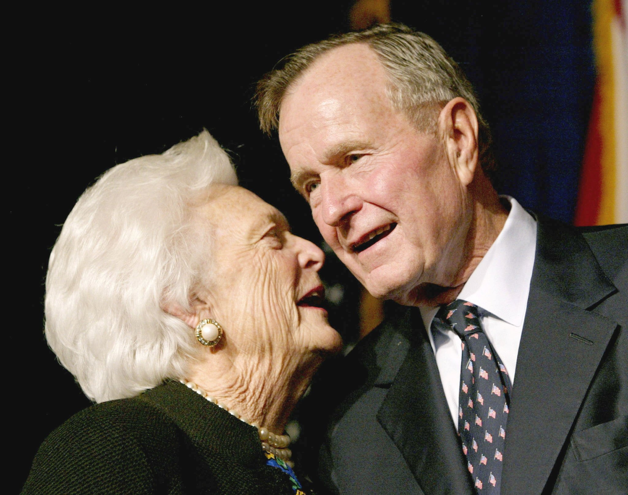 FILE PHOTO: Former U.S. President George Bush speaks with his wife Barbara in Miami