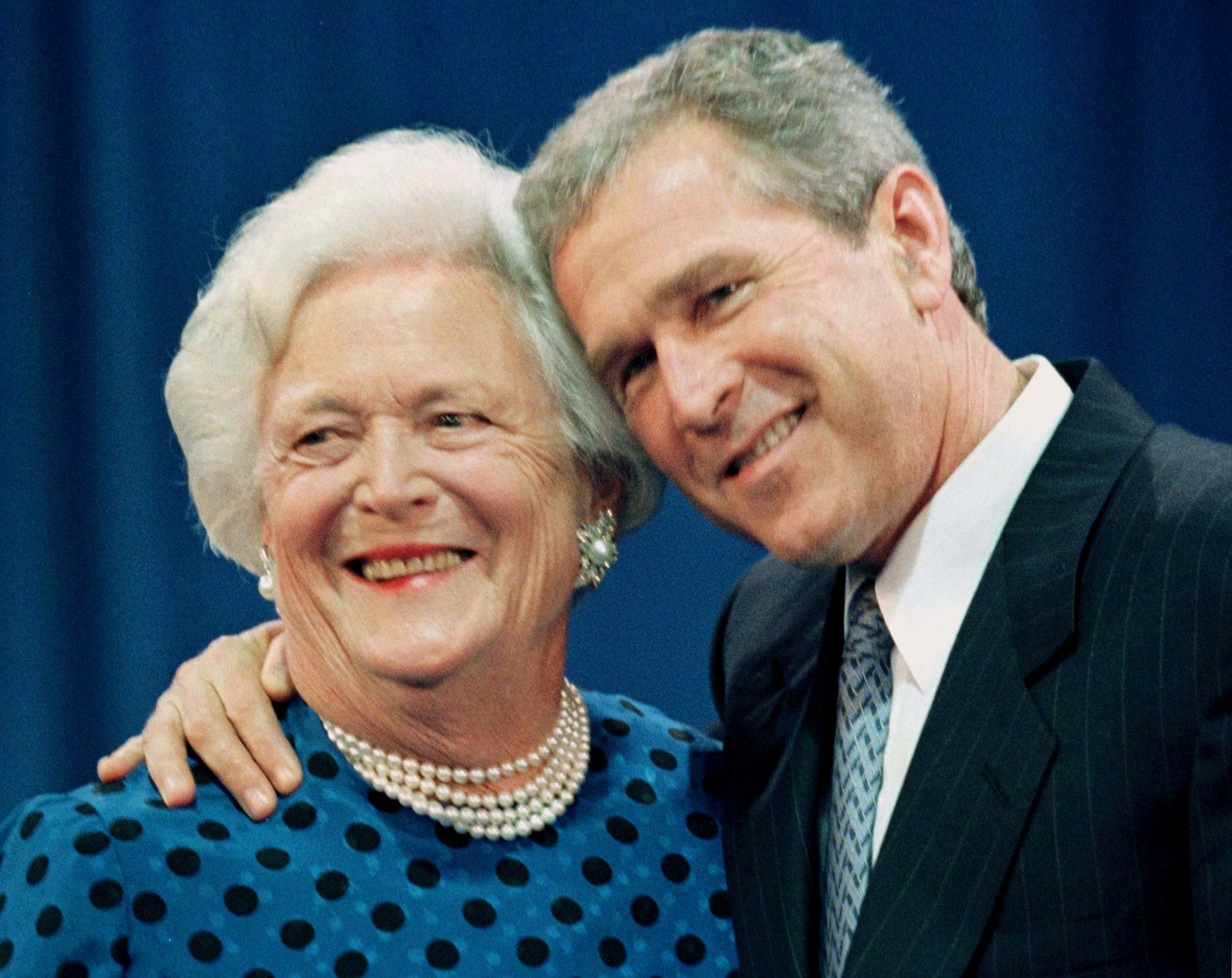 FILE PHOTO: Gov. George W. Bush gives his mother and former first lady Barbara Bush a hug after a family portrait session