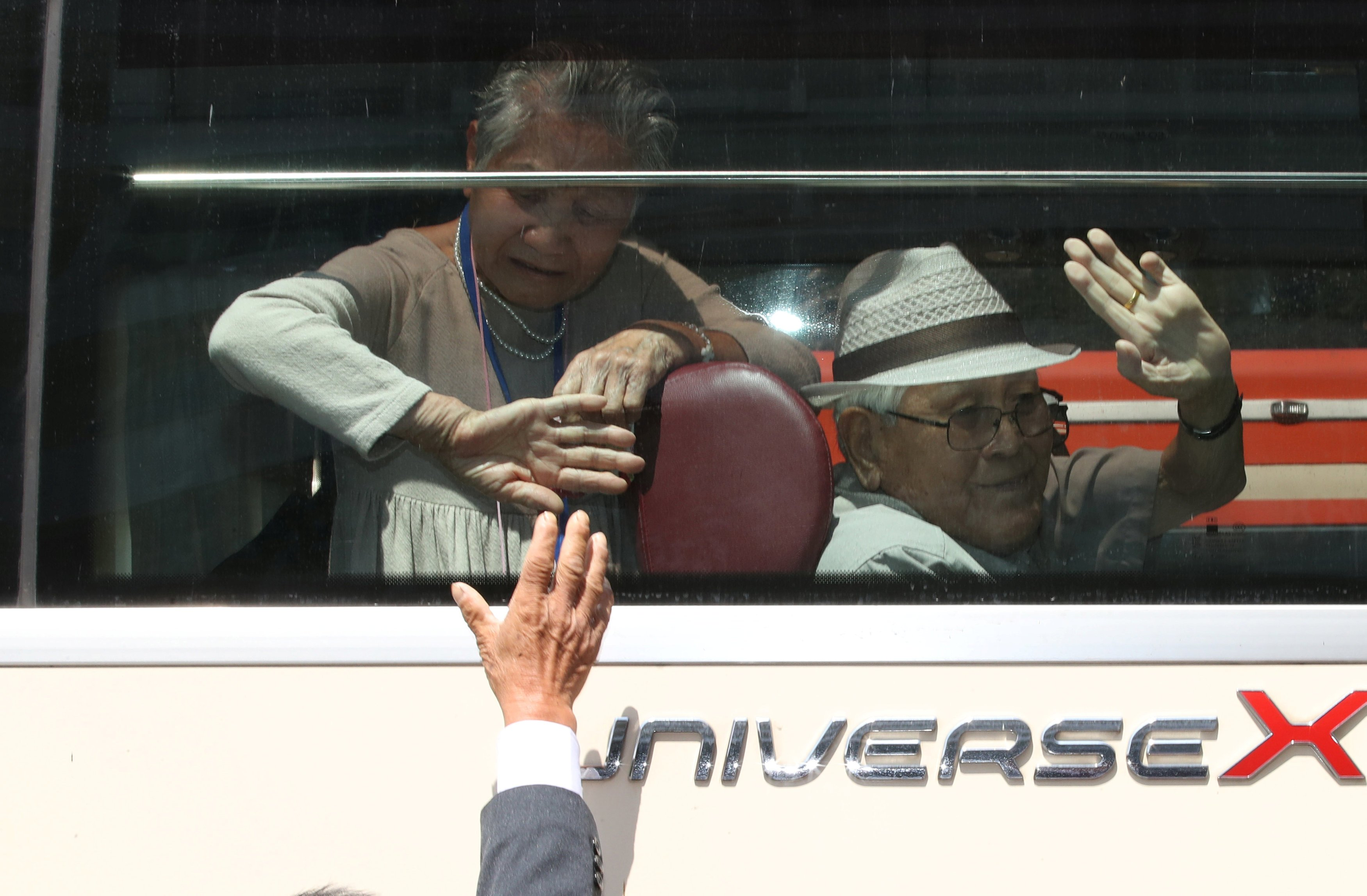 A North Korean man bids farewell to his South Korean family members as they leave after a reunion at Mount Kumgang resort