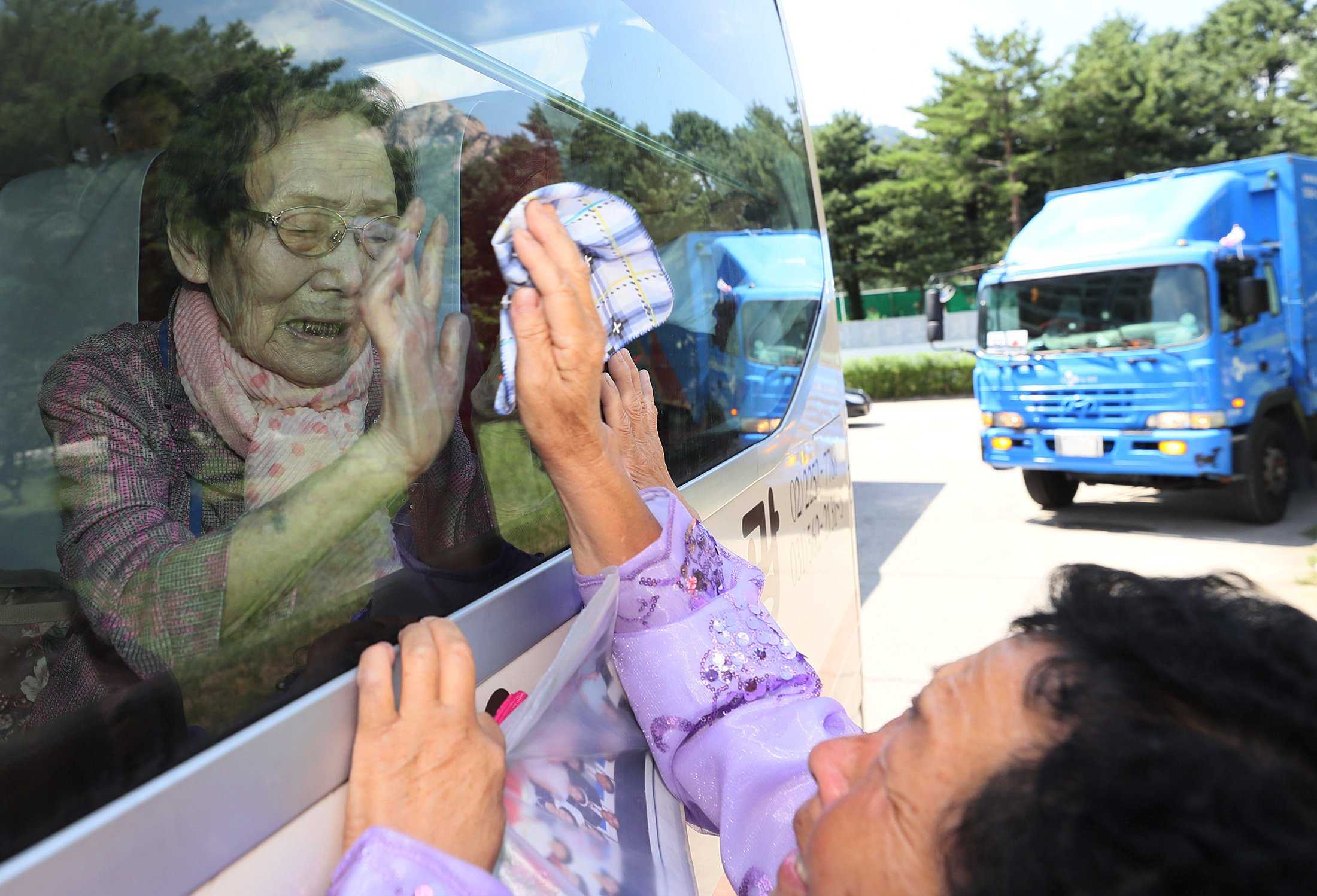 A North Korean woman bids farewell to her South Korean family members as they leave after a reunion at Mount Kumgang resort