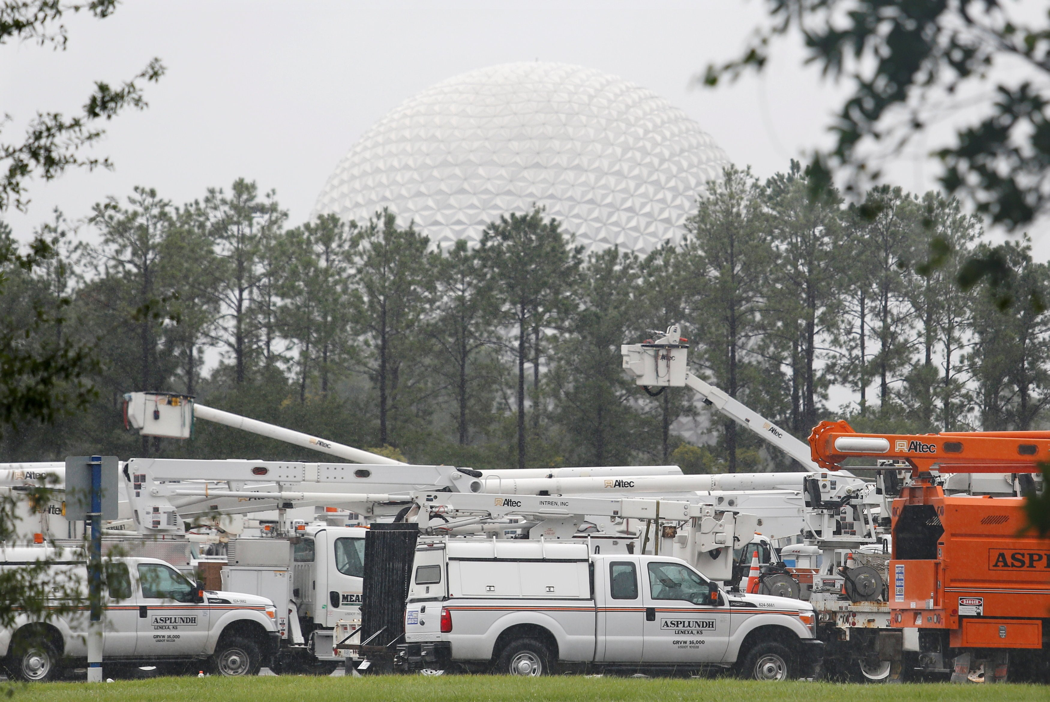 A fleet of utility trucks is parked in a parking lot at Disney's Epcot theme park ahead of the arrival of Hurricane Irma in Kissimmee, Florida
