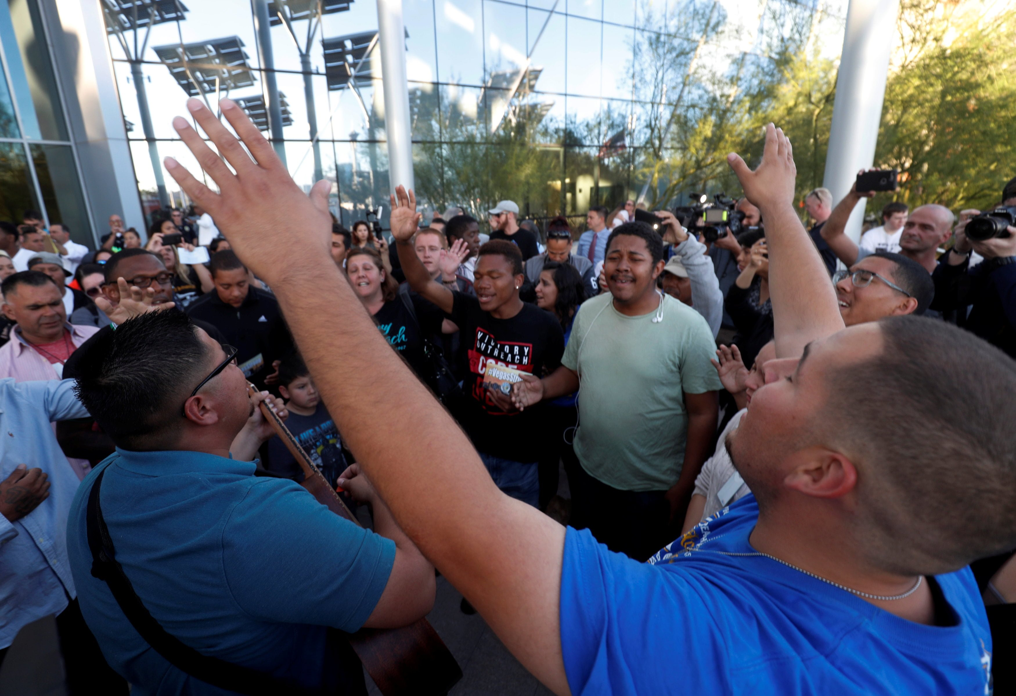 People sing during a prayer vigil in honor of those affected by the shooting in Las Vegas