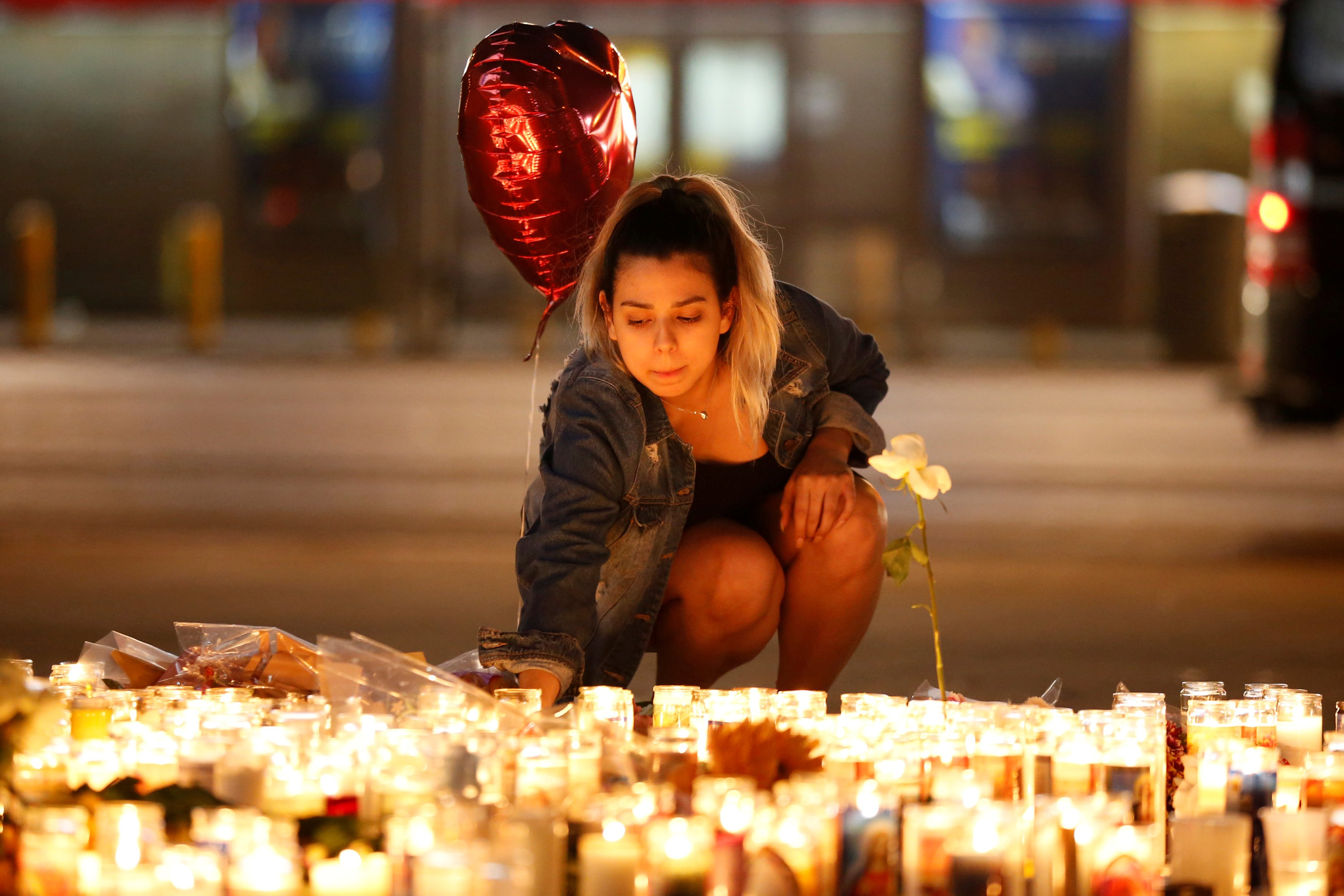 A woman lights candles at a vigil on the Las Vegas strip following a mass shooting at the Route 91 Harvest Country Music Festival in Las Vegas