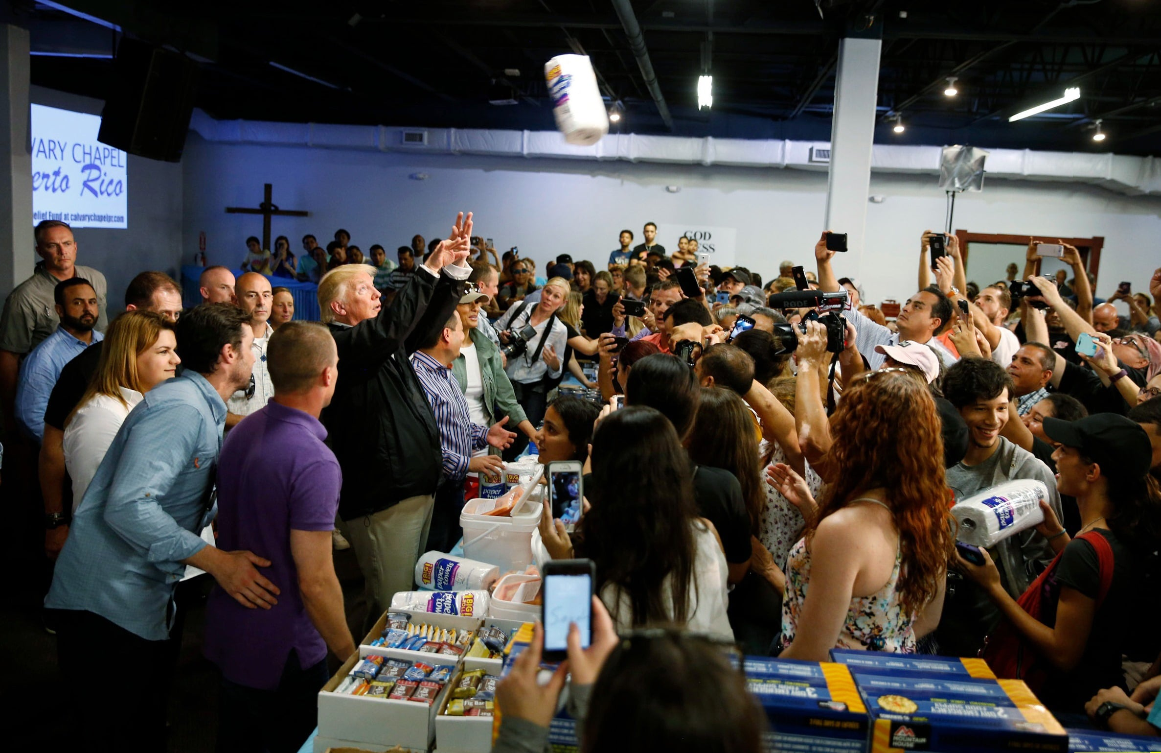 President Trump throws paper towels to residents gathered in a chapel while visiting areas damaged by Hurricane Maria in San Juan, Puerto Rico