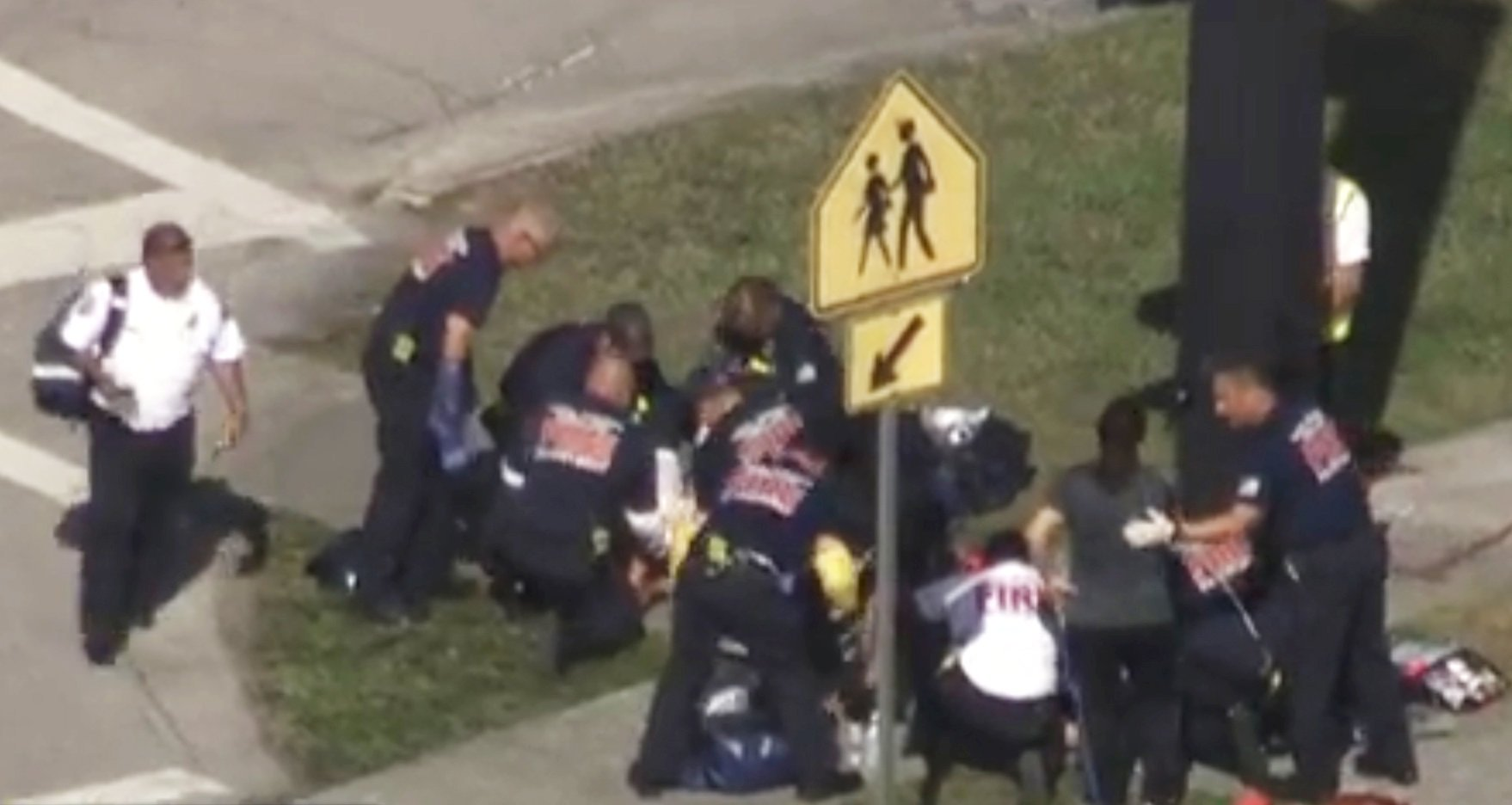 Rescue workers deal with a victim near Marjory Stoneman Douglas High School during a shooting incident in Parkland