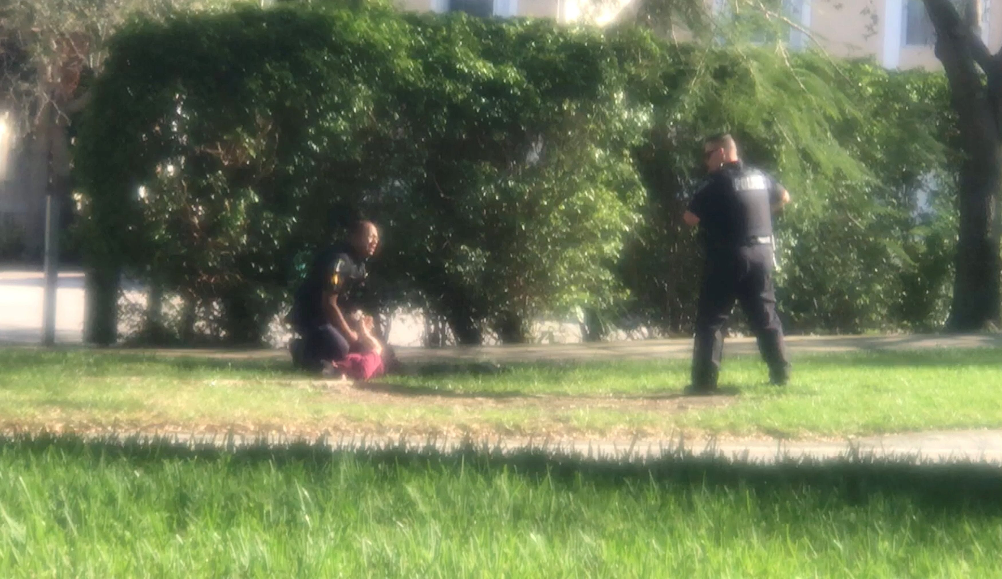 A man is placed in handcuffs by police officer, following a shooting incident in Parkland