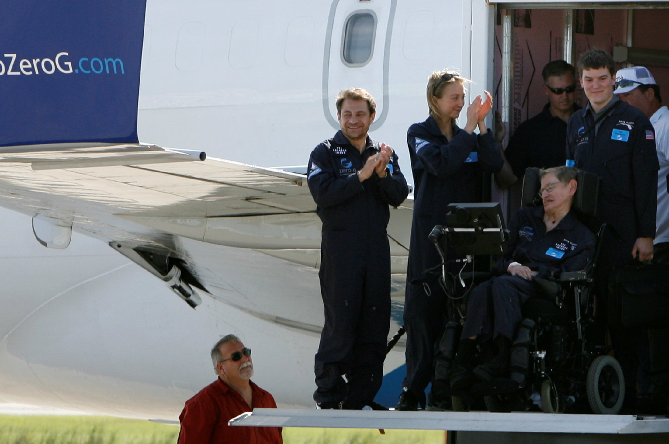 FILE PHOTO: CEO of ZERO-G Peter Diamandis (L) and crew with Professor Stephen Hawking, the world renowned physicist and expert on gravity on a lift truck after his flight at  Kennedy Space Center in Cape Canaveral, Florida