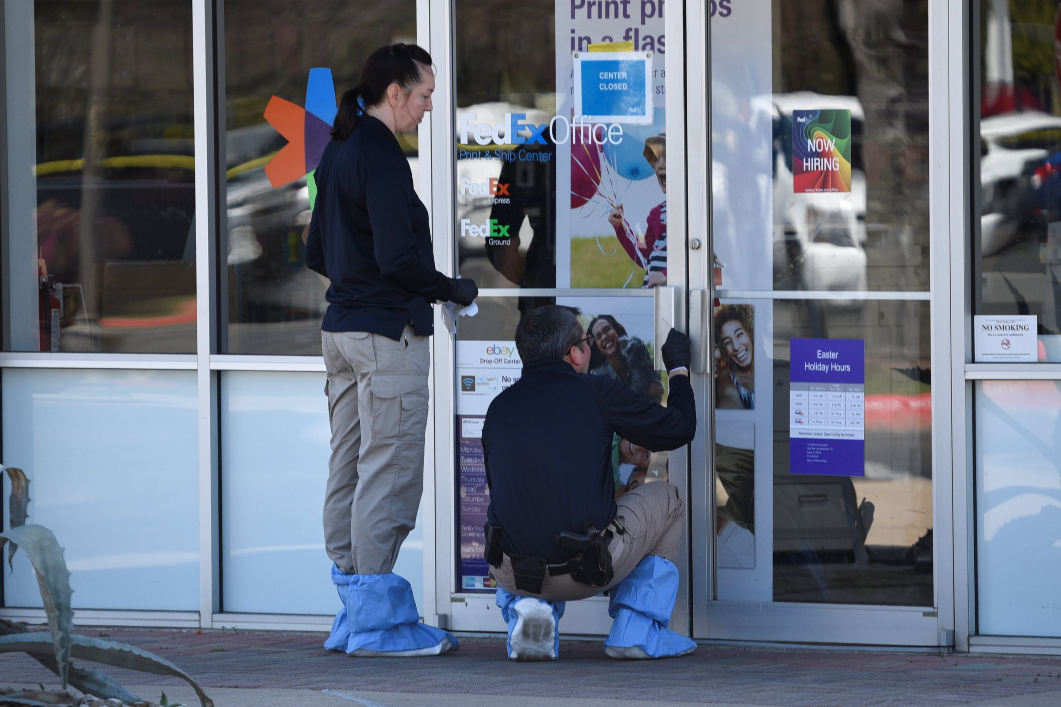 Law enforcement personnel are seen gathering evidence outside a FedEx Store which was closed for investigation, in Austin, Texas