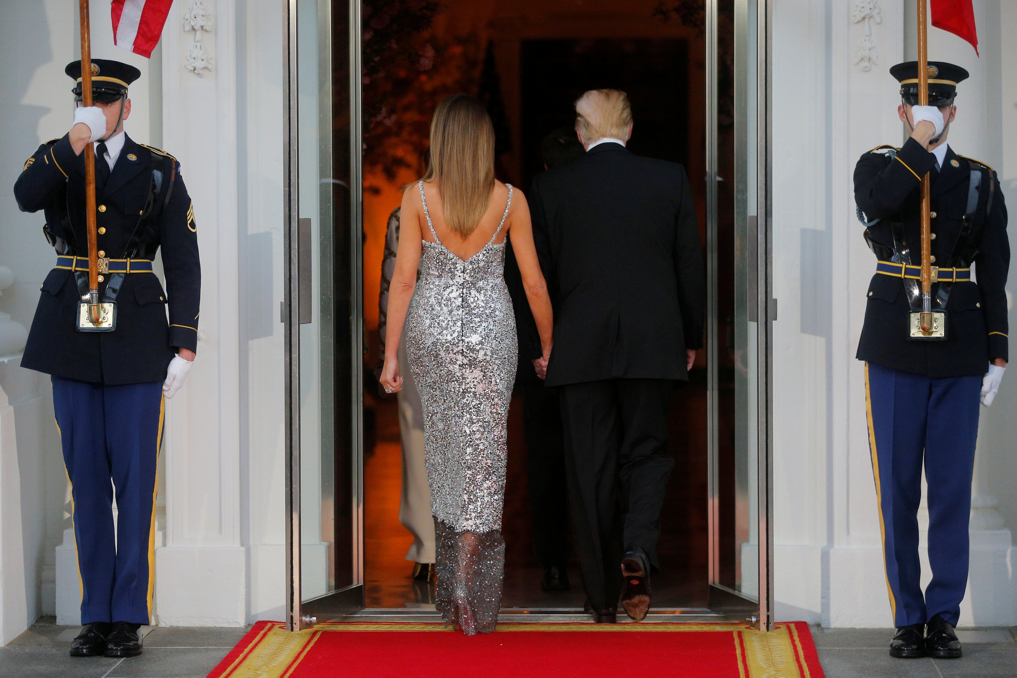 U.S. President Trump and first lady Melania walk into the White House after welcoming French President Macron and his wife for a State Dinner in Washington
