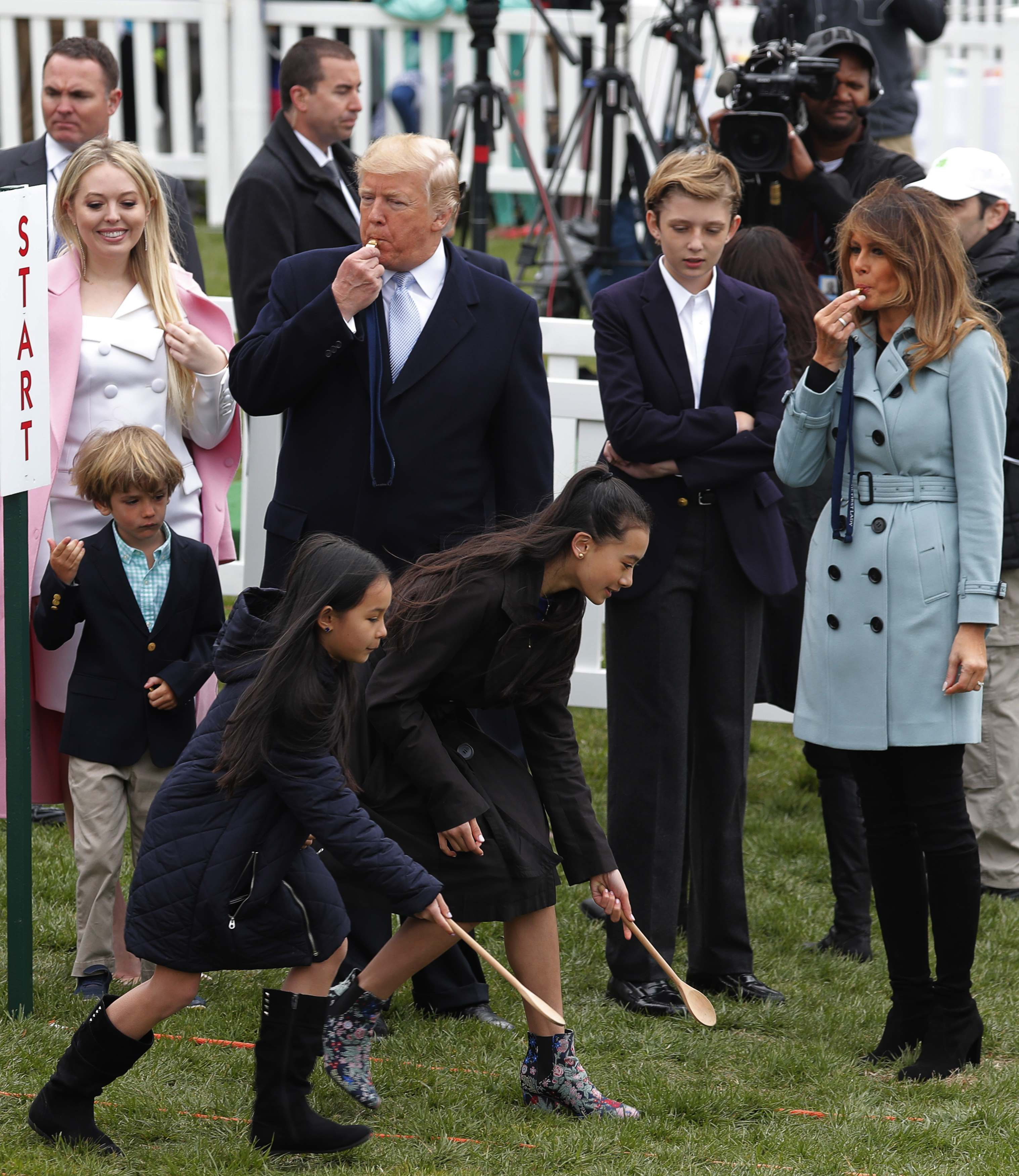President Donald Trump and first lady Melania Trump blow whistles at the annual White House Easter Egg Roll on the South Lawn of the White House in Washington