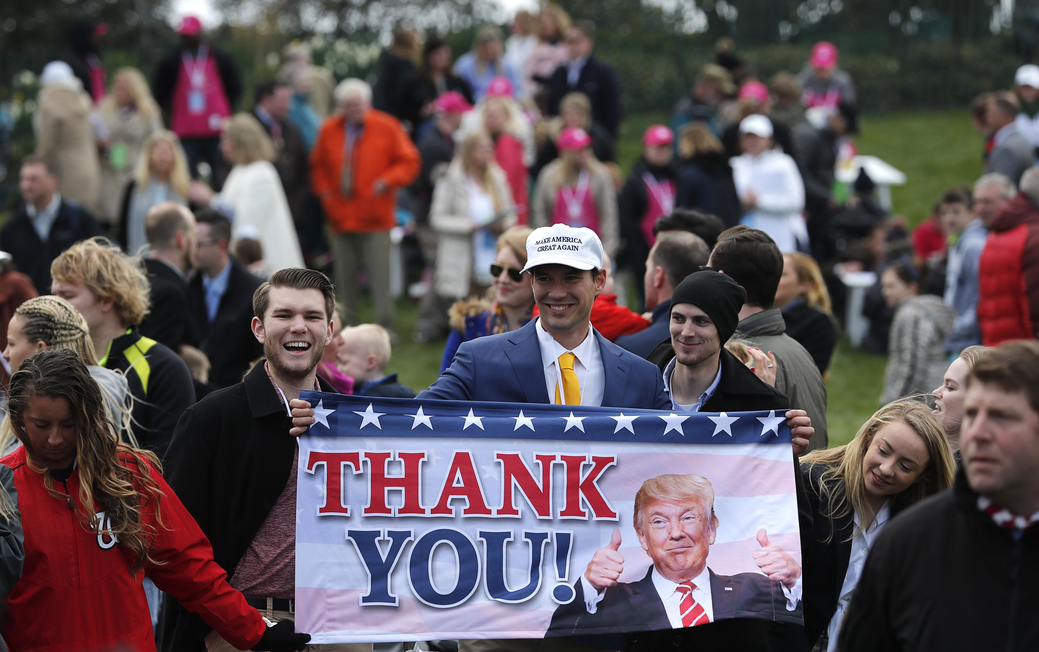 """Supporters of U.S. President Donald Trump hold a """"Thank You!"""" banner at the annual White House Easter Egg Roll on the South Lawn of the White House in Washington"""