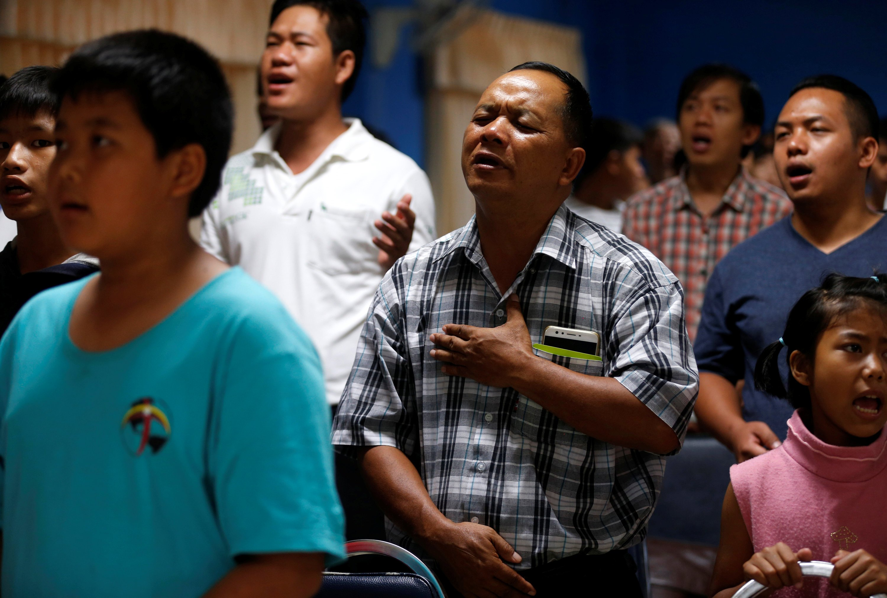 Relatives and friends pray for the 12 schoolboys and their soccer coach tapped inside a flooded cave, at Mesai Grace Church  in the northern province of Chiang Rai