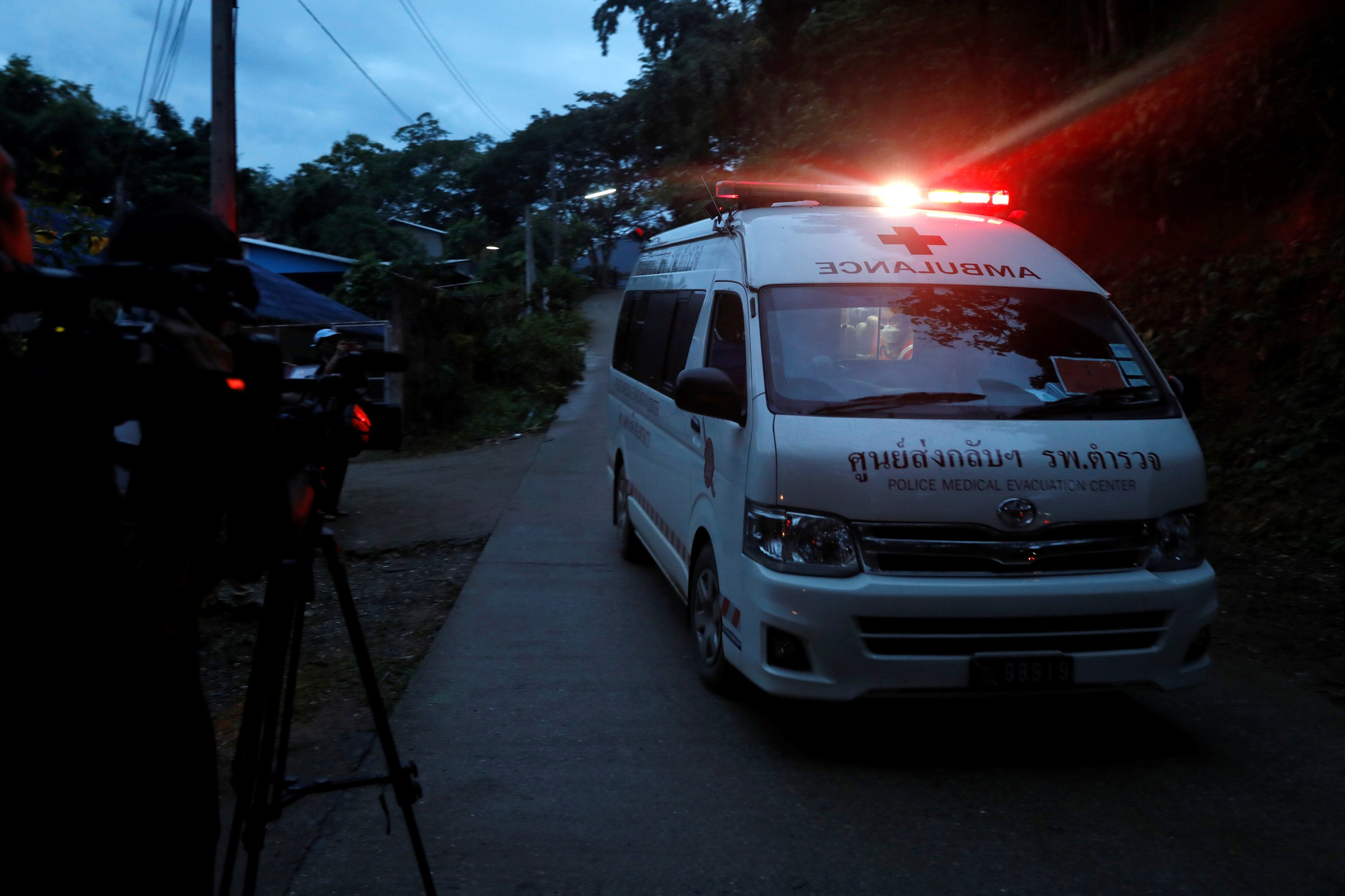 Journalists film an ambulance believed to be carrying rescued schoolboys as it travels to a military helipad near Tham Luang cave complex in the northern province of Chiang Rai