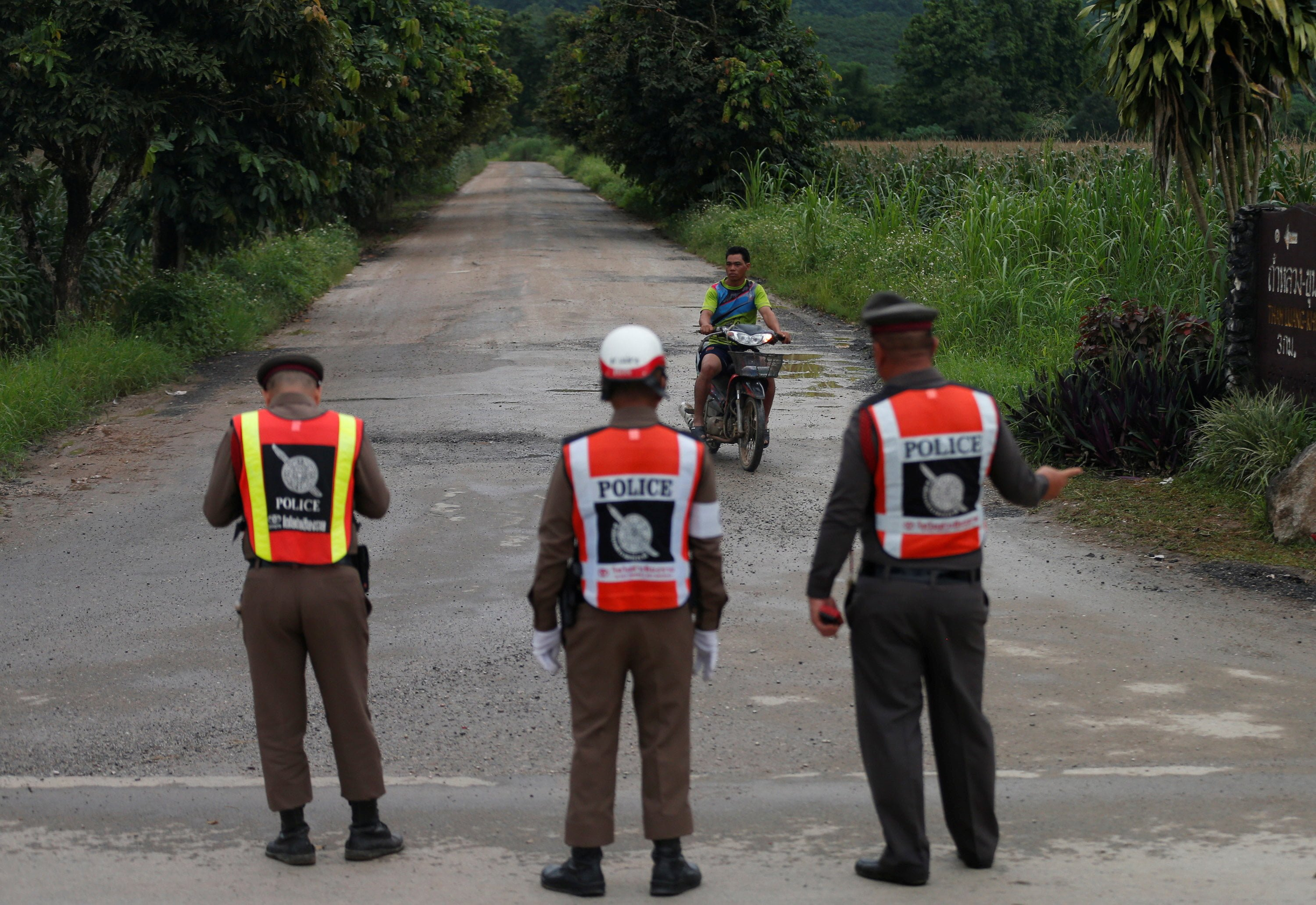 Police officers block a road leading to Tham Luang cave complex in the northern province of Chiang Rai